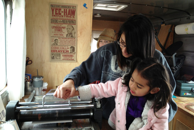 Two participants at Denver Public Library's Community Learning Plazas create a monoprint on a traveling printing press studio.