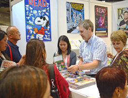 Michael Dowling (in striped shirt) and former ALA President Loriene Roy (right) assist IFLA attendees at the ALA exhibit booth in Singapore. Photo by Carlon Walker