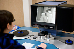A patron at the Indiana University Library Film Archive uses a flatbed viewer to watch a 16mm archival film.