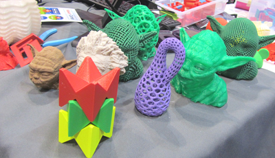 Several Yoda heads mingle with other 3D-printed object d'art at Maker Monday