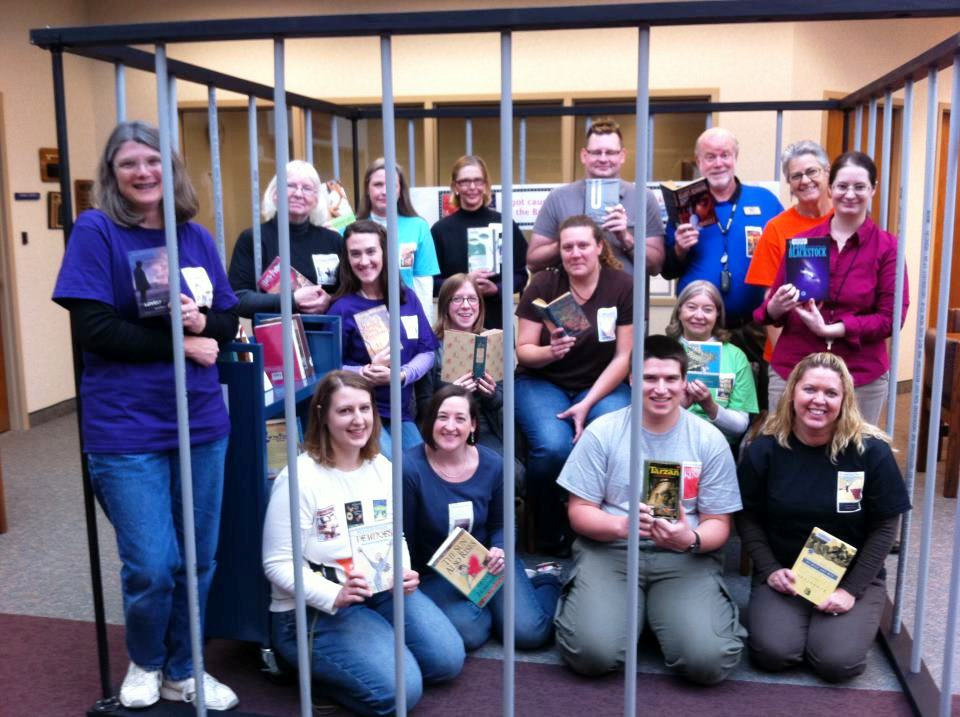 Staff members at Brownsburg (Ind.) Public Library, some wearing special T-shirts, read banned books in a makeshift jail.
