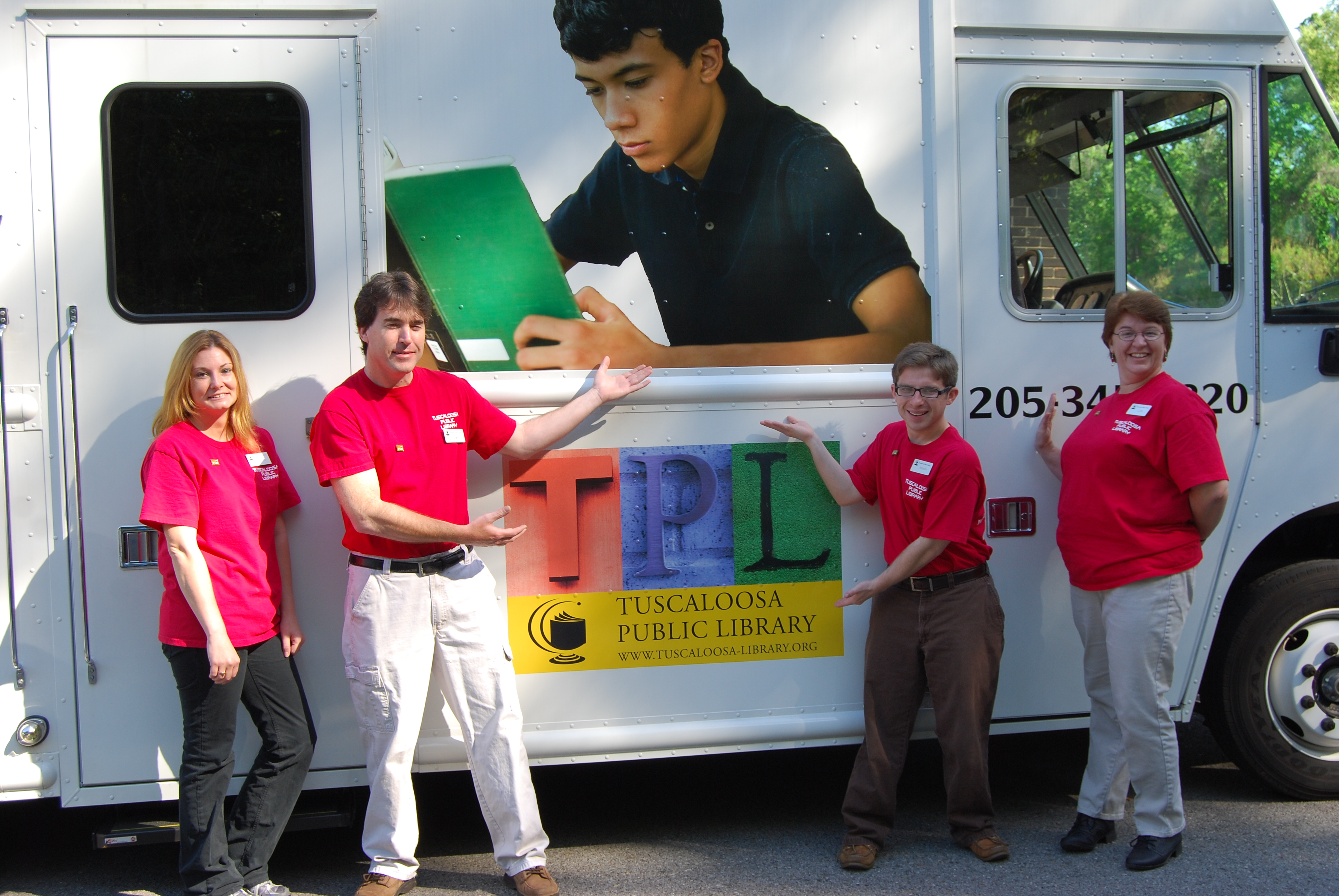 Staffers (left to right) Tammy Adams, Kelly Butler, Addison Canevaro, and Lynn Allen show off the Tuscaloosa (Ala.) Public Library bookmobile during National Bookmobile Day April 13, as part of NLW.