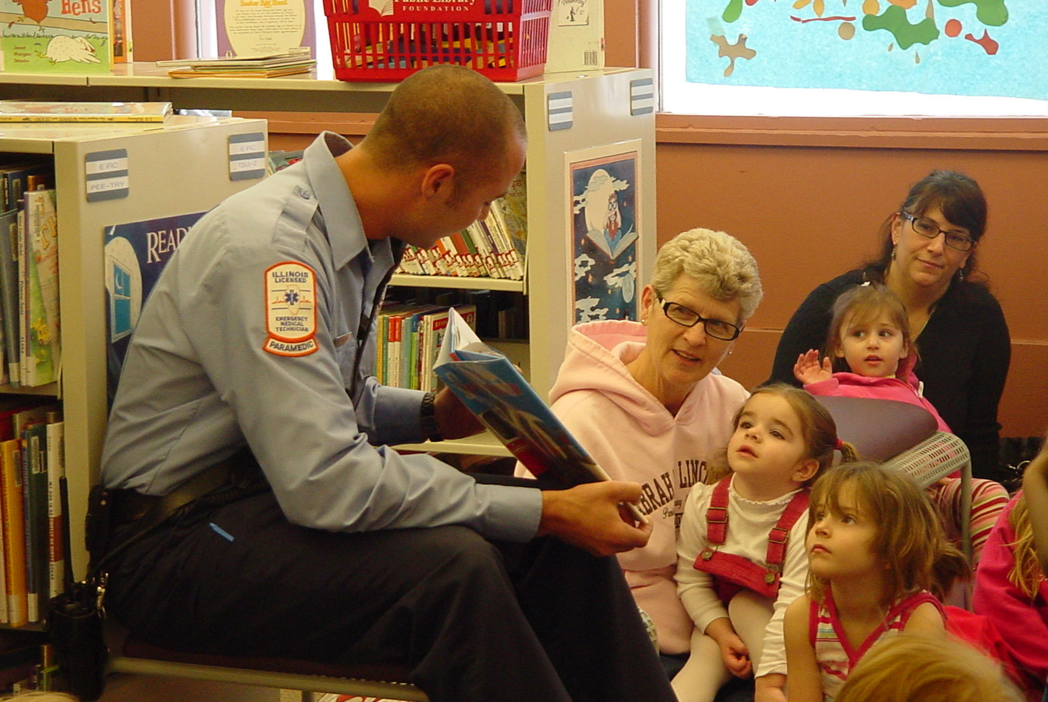 "Rock Island firefighter Chad Chindlund of the Central Fire Station reads to children at Rock Island (Ill.) Public Library's 30/31 branch. The library's Children's Department hosted special ""Community Helper"" storytimes with volunteer readers from the police and fire departments."