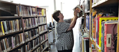 Driftwood Librarian Kathy Bates shelves a book in the new library building in Lynn, Arkansas. Photo by Kenneth Heard
