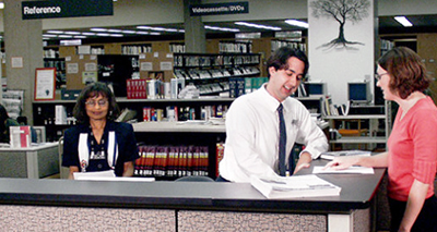 Dale Heath (wearing a tie) at the reference desk before her transition