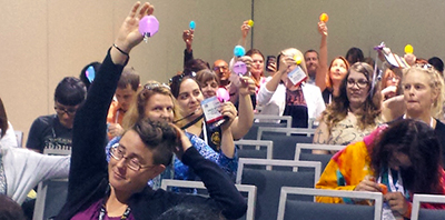 Attendees hold up their completed LED paper gems