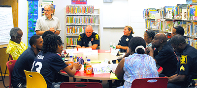Richard Frieder (standing), community engagement director at Hartford Public Library, facilitates a community dialogue among neighborhood residents and Hartford police officers on the topic of community violence and public safety. The dialogue took place in June 2015 at Hartford Public Library's Barbour Street branch. Photo by Judy Wyman Kelly