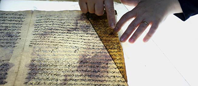 A member of the library restoration staff works on a damaged manuscript at the Iraq National Library