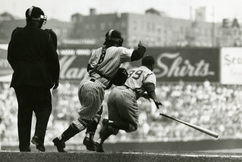 At Yankee Stadium during the 1955 World Series, Brooklyn batter Roy Campanella and New York catcher Yogi Berra both start toward first base: Campy attempting to beat out his grounder and Yogi preparing to back up the play.