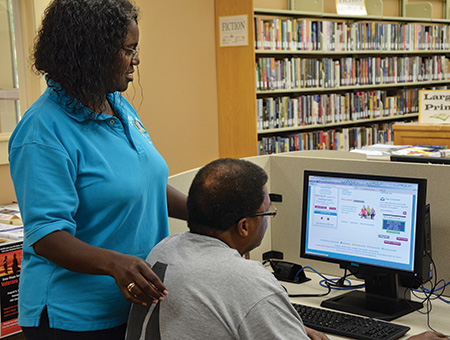 Marilynn Lance-Robb, branch manager at the Carvers Bay Branch Library in Georgetown, South Carolina, assists a patron with health information.