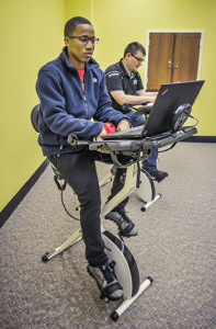 Troy University students ride the new exercise-study hybrid bikes at the Troy campus library. (Photo: Kevin Glackmeyer)