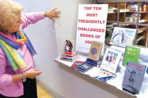 Jo Roussey, director of volunteer services at York County (Pa.) Libraries' Martin branch, sets up a display of the top 10 books most frequently challenged or requested to be removed from libraries last year.