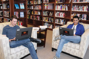 Utah Lambert (left) and Jonathan Manning use the new laptops available for checkout at Anythink Brighton in Colorado.