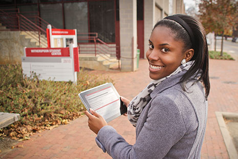 North Carolina State University student Tova Williams uses a tablet to tour campus with an eye toward African-American history at the university. Williams is using an app called Red, White, and Black, which started as a collaboration between NCSU's Digital Library Initiative, the tour's creators, and the library's special collections. Photo: Charles Samuels, NCSU Libraries