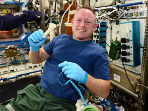 ISS Commander Butch Wilmore holds up the ratchet after removing it from the print tray.