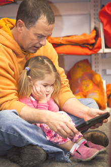 Chloe Warwick and her dad Mark Warwick get absorbed in a Harford County (Md.) Public Library iPad mini. Photo by J. Thomas Photography