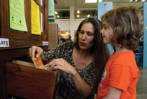 Rebecca Newburn helps a young patron explore the Richmond Grows Seed Lending Library in Richmond, California.