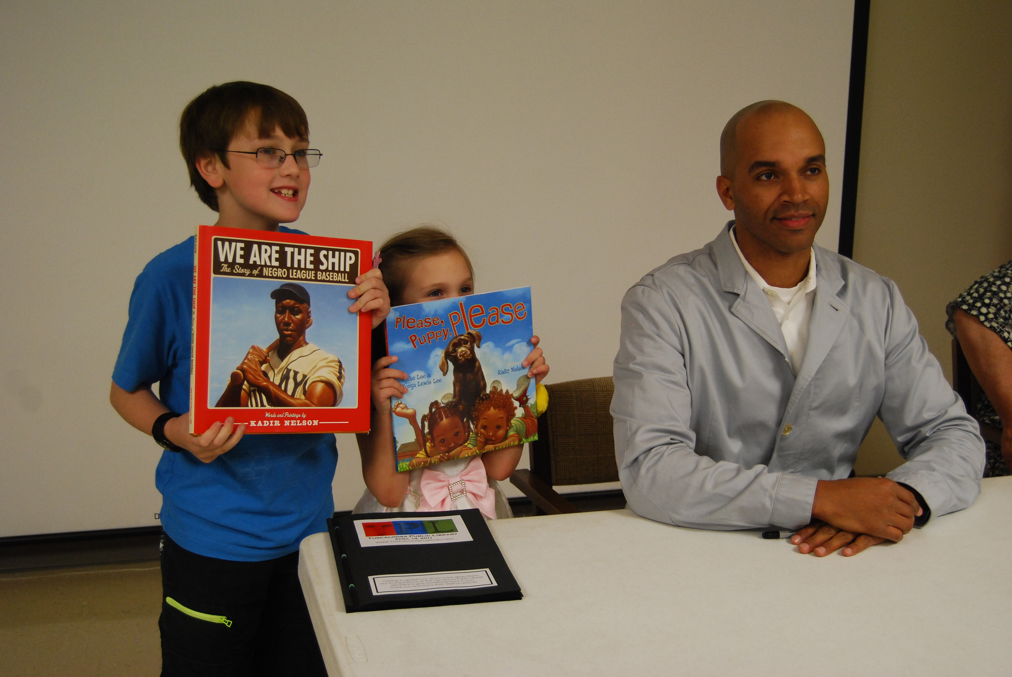 Award-winning author and illustrator Kadir Nelson joins (from left) Blaine and Kyra Richardson during a book signing at Tuscaloosa (Ala.) Public Library's main branch.