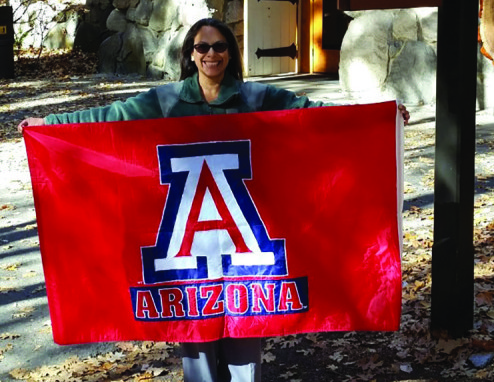 Virginia Sanchez, librarian at Yosemite National Park, poses with a flag from the University of Arizona, her alma mater.