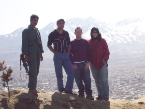 Andrea Muto standing next to an American project colleague, a driver, and a military guard on top of a mountain in Kabul, Afghanistan, in 2007.