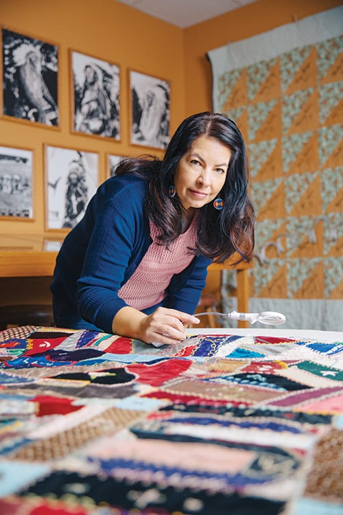 Archivist Tawa Ducheneaux stands over a quilt that dates to between 1913–1915. Each square was created by quilting club members from the Wounded Knee ­District in South Dakota and notes the maker's identity, the date, and sometimes the family's cattle brand.