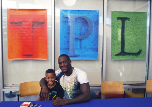 World Boxing Council world heavyweight champion Deontay Wilder with Tuscaloosa (Ala.) Public Library patron Jaden Williams during Wilder's book signing. (Photo: Vince Bellofatto)
