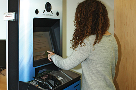 A patron renews her driver's license inside Ames (Iowa) Public Library in June. Iowa DOT unveiled 11 kiosks in libraries in May.