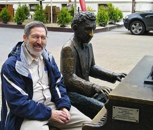Sapon-White sits next to a bronze statue of pianist Arthur Rubenstein in Łódz, Poland. Photo: Richard E. Sapon-White