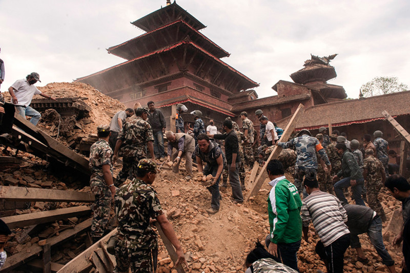 Workers remove rubble and earth from the foot of a temple destroyed in the April 25 earthquake in Nepal. Photo: Shutterstock.com