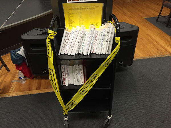 "A black rolling library cart stacked with books was wrapped in yellow tape bearing the phrase Art + Activism. On its shelves are books with fake covers masking the real ones, their spines displaying the reasons they were challenged—""Violence,"" ""Filth,"" ""Dirty Talk."""