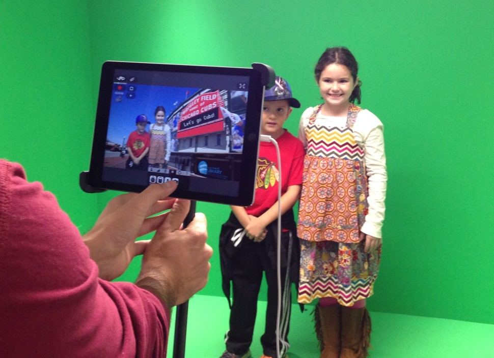 Digital Services Assistant Srdjan Vasilic takes a photo of two patrons in front of the green screen in Niles Public Library's Creative Studio.
