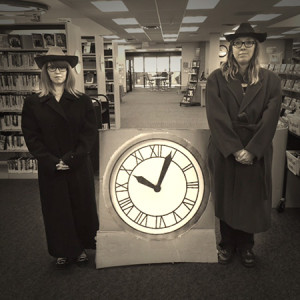 """At Jefferson County (Colo.) Public Library, patron experience associate Lindsay Masciotti (left) and patron experience supervisor Kelly Duran pose with a replica of the clock tower featured in the <i>Back to the Future</i> films. <span class=""""credit"""">Photo: Jefferson County Public Library</span>"""