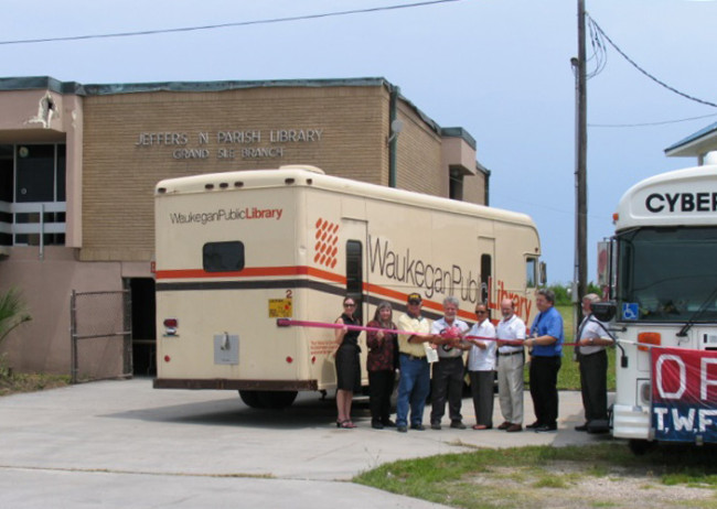 Jefferson Parish (La.) Library staff stands near a bookmobile from Waukegan (Ill.) Public Library and cybermobile from Muncie (Ind.) Public Library outside of the destroyed Grand Isle branch post-Katrina.Photo: Jefferson Parish Library