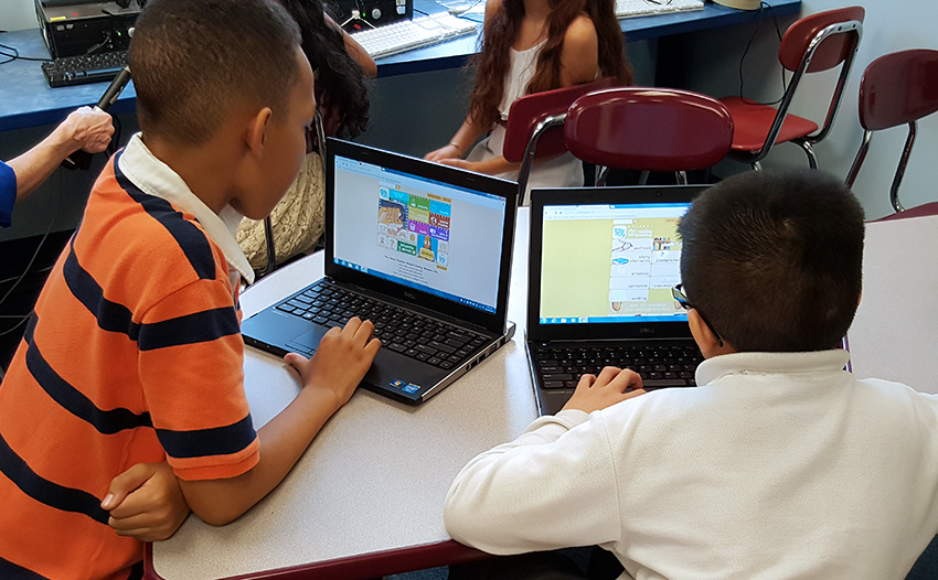 Kaiden Lewis and Kevin Ren use laptops in Thomson Elementary School's library classroom to code.