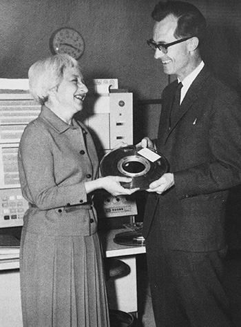 Henriette Avram presents a magnetic tape containing 9,300 records to Richard Coward of the British National Bibliography, 1967. Photo: American Libraries, October 1989