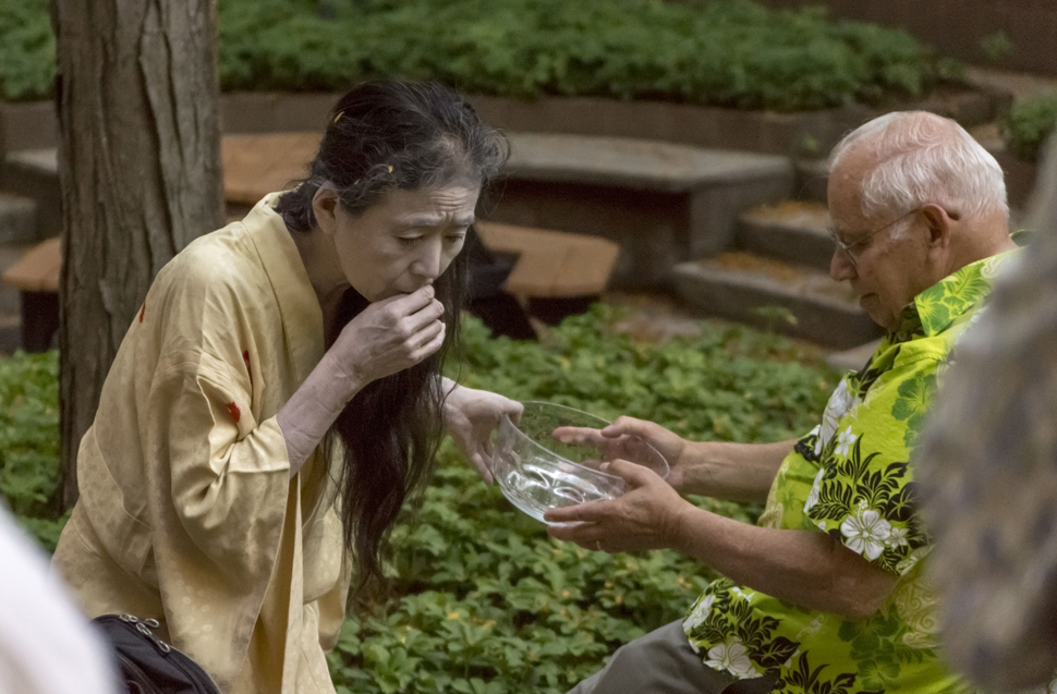 Eiko Otake offers a bowl of water to Russell Library Director Arthur Meyers. Otake's performances often allow audience members to participate and react to elements of the dance.