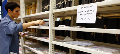Archivist Mathilde Puntault puts up for drying some drawings from the Bataclan on shelves at the Paris Archives. Photo by Francois Mori/Associated Press