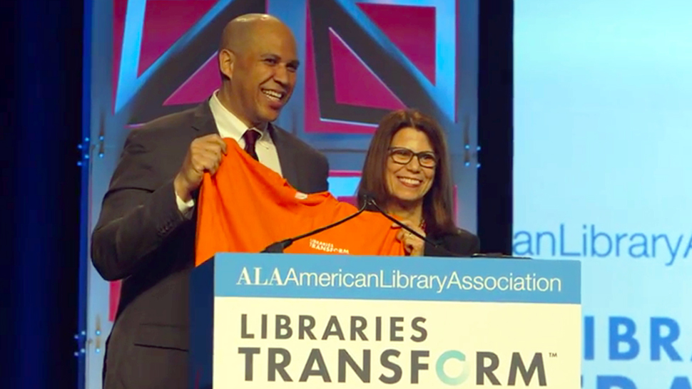 ALA President Sari Feldman presents Sen. Cory Booker a Libraries Transform t-shirt.