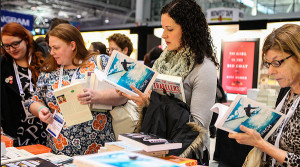 Alison Griffin (middle), Vancouver, Canada, looks at books in the exhibit hall along with other attendees.