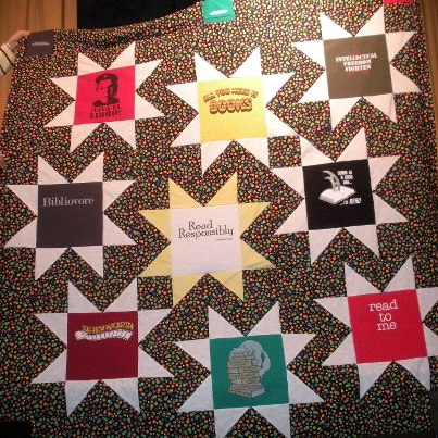 """Unshelved Stars,"" designed by Jill Patterson, manager of the La Habra California Branch Library and quilted by Kelly Sattler, head of web services at Michigan State University Libraries in East Lansing, features T-shirts donated from Unshelved comic strip publisher Overdue Media. The stars honor librarians, books, authors, and libraries, and the quilt was auctioned at the 2013 Annual Conference in Chicago."