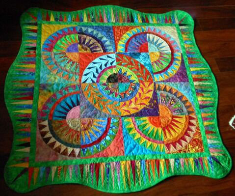 "Based on the ""Batik Wheels"" design by Deb Karasik, ""BibiloQuilters Batik Wheels"" is another collaborative quilt coordinated by Kelly Sattler that uses bright colors and separate blocks contributed from numerous BiblioQuilters members."