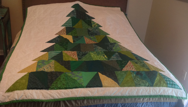 """Evergreen"" by Debra Rollins, a retired librarian from Louisiana State University at Alexandria, uses a variety of green fabrics contributed from various quilters and was auctioned off at the 2015 ALA Annual Conference in San Francisco."