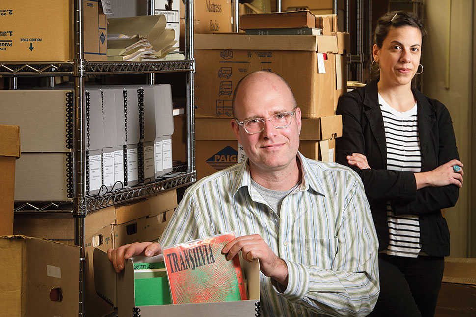 Frank Bridges, media studies doctoral student, and Christie Lutz, New Jersey regional studies librarian and head of public services in Special Collections and University Archives, with items in the New Brunswick Music Scene Archive at Rutgers University.