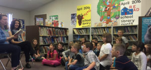 Author Megan McDonald (far left) reads to kids during a School Library Month event.