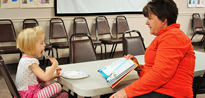 Ruth VanScoyk, right, reads a Dr. Suess book to her granddaughter, Ellery VanScoyk, 4, who is busy polishing off a pancake