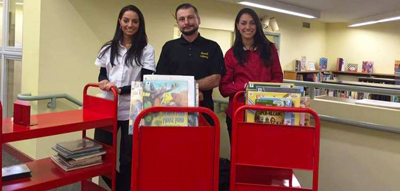 Shane Grant, of the Russell Library maintenance staff, with Adriana (left) and Sabrina Indomenico, owners of Santostefano Auto Body. The auto body shop painted the carts for free