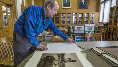 Brian Kamens, supervisor of the Northwest Room who has worked there since 1982, looks at the library's collection of Edward Curtis photographs of Native Americans from the early 1900s. Dean J. Koepfler, The News Tribune