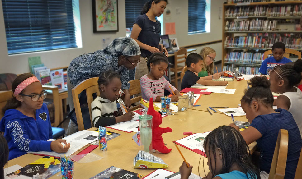 Barbara Prince and YuChieh Chien (standing, from left) assist students in writing their first-draft letters to famous Amys at the Garfield Park Lending Library in New Castle, Delaware.Photo: Sophia Hanson