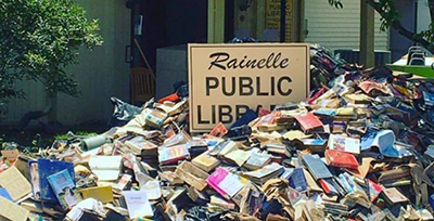 Water-soaked books await pickup outside the flooded Rainelle (W.Va.) Public Library