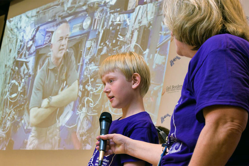 Fifth-grader Evan Sass asks NASA astronaut Jeff Williams a question via video chat while Denise Raleigh, Gail Borden Public Library's division chief of public relations and development, holds the microphone. The Elgin, Illinois, library was one of eight nationwide selected for the traveling exhibit, Discover Space: A Cosmic Journey. Photo: Jason Brown